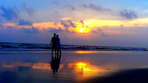 Couple walking at the beach during sunset