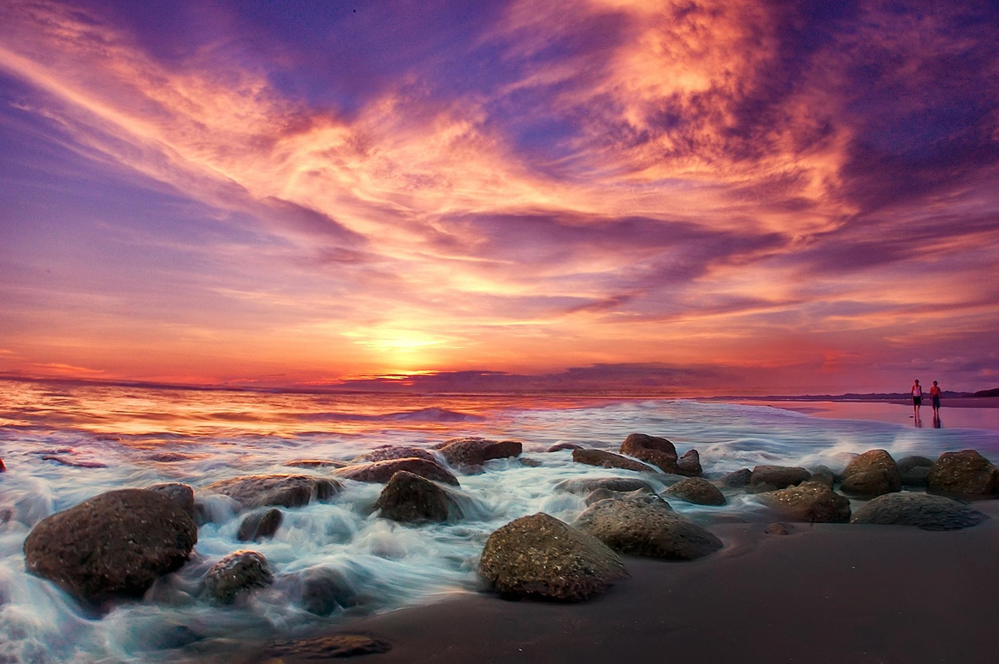Long Exposure sunset photo waves crashing onto rocks